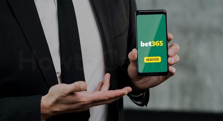मैन bet365 कैसीनो पेज के साथ मोबाइल पकड़े हुए