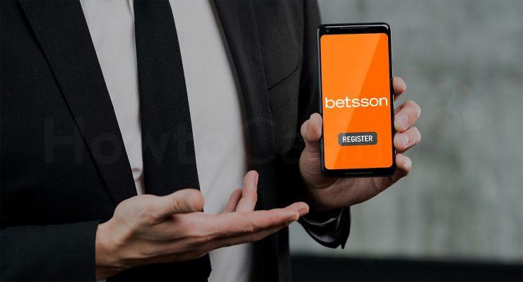 बेट्सन कैसीनो पेज के साथ मोबाइल पकड़े हुए आदमी
