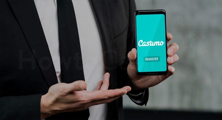 कैसुमो कैसीनो पेज के साथ मोबाइल पकड़े हुए आदमी