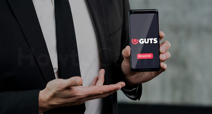 Man holding mobile with Guts Casino page