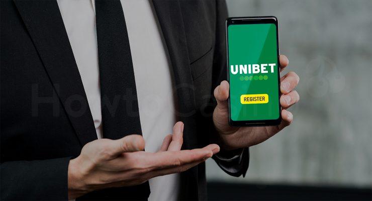 आदमी मोबाइल पकड़े हुए Unibet कैसीनो पेज