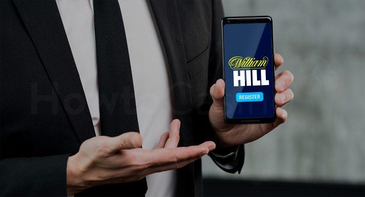 विलियम हिल कसीनो पेज के साथ मैन मोबाइल पकड़े हुए